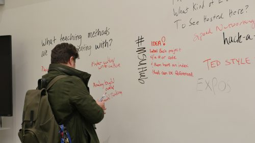 An open house visitor answers a question on one of our writeable walls.