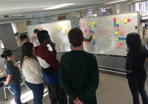 Students stand in front of a whiteboard with sticky notes on it.