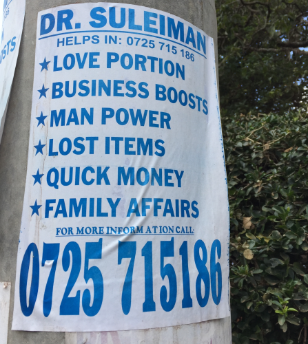 A white flyer attached to a post with blue text advertising services for Dr. Suleiman. Services include: love portion, business boosts, man power, lost items, quick money, and family affairs. The Doctor's phone number is in large text at the bottom.