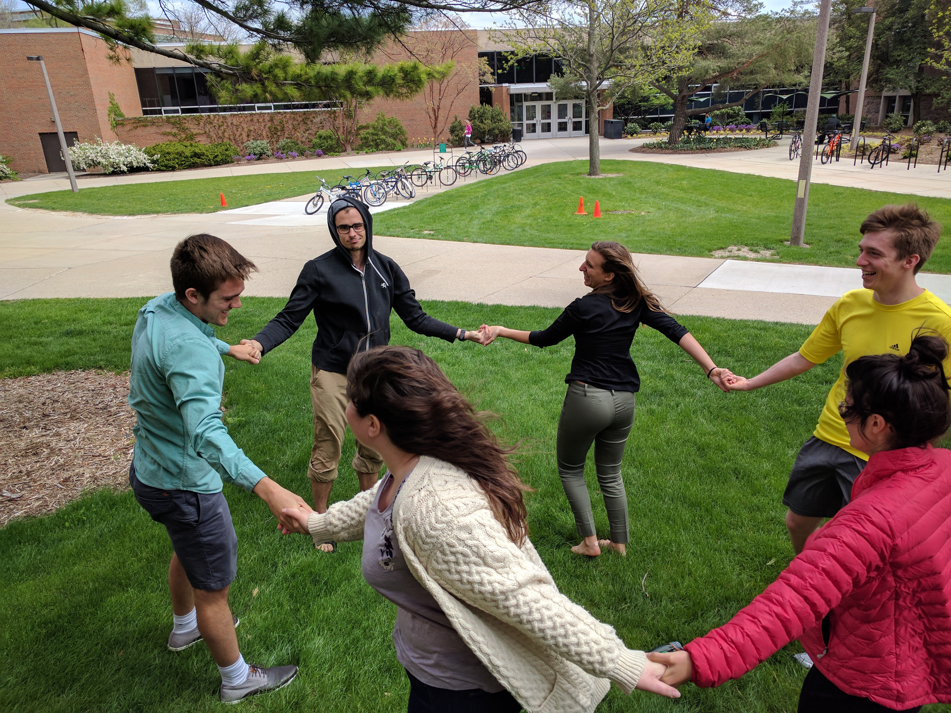 A group of six students hold hands in a circle outside in the grass.