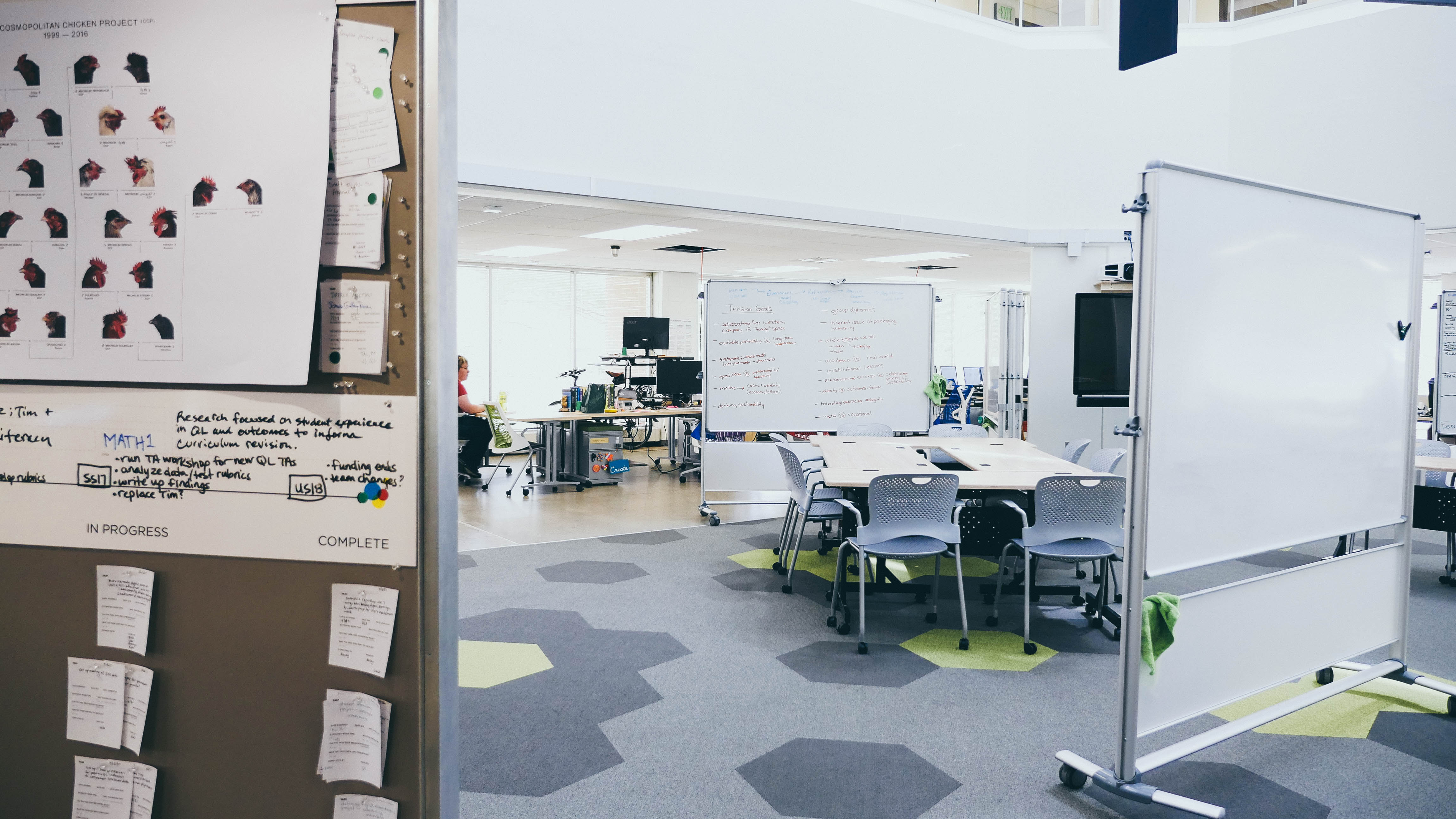 Whiteboards stand in a space with hexagon-tiled carpet, surrounding a table and chairs.