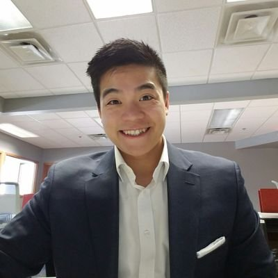 Tommy Truong smiling in a suit