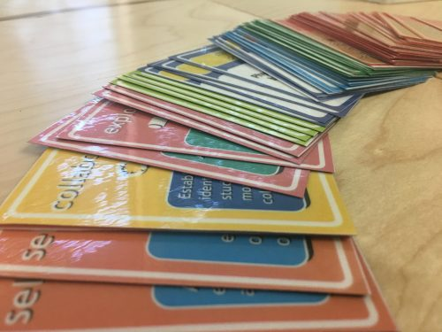 A stack of cards from the active learning game are spread out on a wooden table.