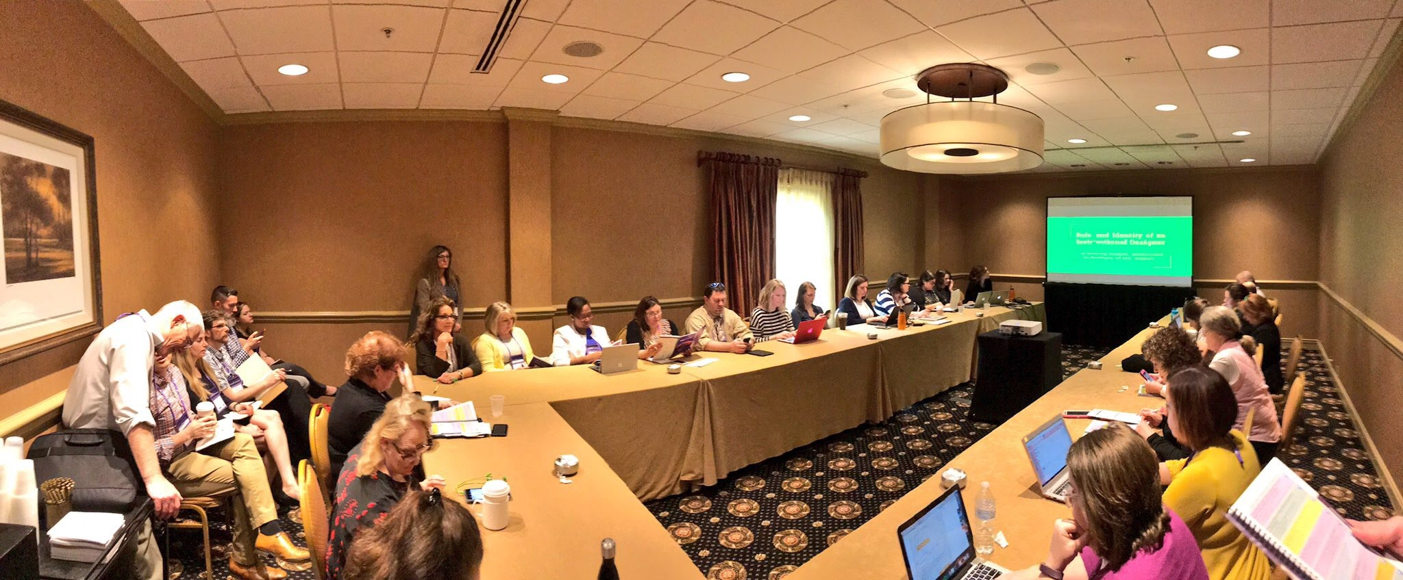 A group of professionals sit in a session at OLC Innovate.