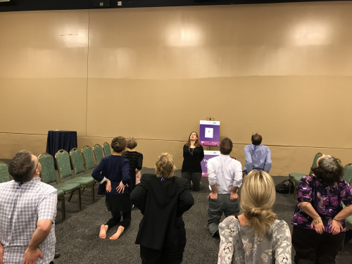 A group of people in professional clothes do yoga at the OLC Innovate Conference.