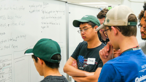Students around a white board in the Hub's flex space looking perplexed.