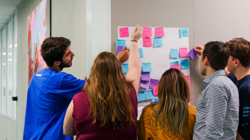 Students in the Hub's flex space putting pink, blue and purple sticky notes on a board.