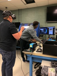 a man is wearing the VR headset while a student manages the simulation on the computer