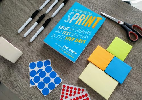 sprint book with office supplies used in design sprint process